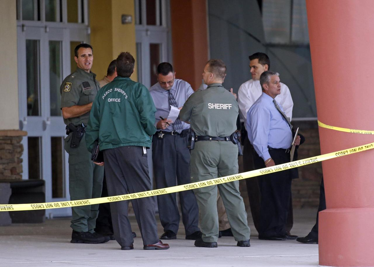Pasco County Sheriff Chris Nocco (L) speaks with investigators as police tape surrounds the Cobb Grove 16 movie theater in Wesley Chapel, Florida January 13, 2014. Authorities took a male suspect into custody after a shooting inside the theater on Monday, injuring two people who were air lifted to a hospital. REUTERS/Mike Carlson (UNITED STATES - Tags: CRIME LAW)
