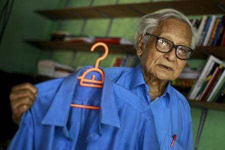 Win Tin poses in one of his prison issued shirts as he shows another one of the blue shirts at his home in Yangon