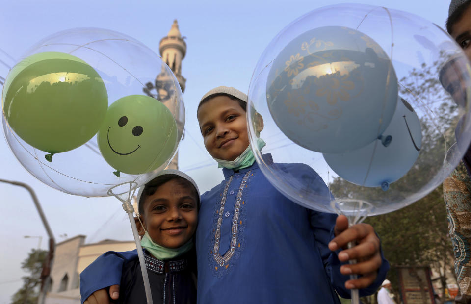 Muslim boys hold balloons after performing an Eid al-Fitr prayer at a mosque in Karachi, Pakistan, Thursday, May 13, 2021. Millions of Muslims across the world are marking a muted and gloomy holiday of Eid al-Fitr, the end of the fasting month of Ramadan - a usually joyous three-day celebration that has been significantly toned down as coronavirus cases soar. (AP Photo/Fareed Khan)