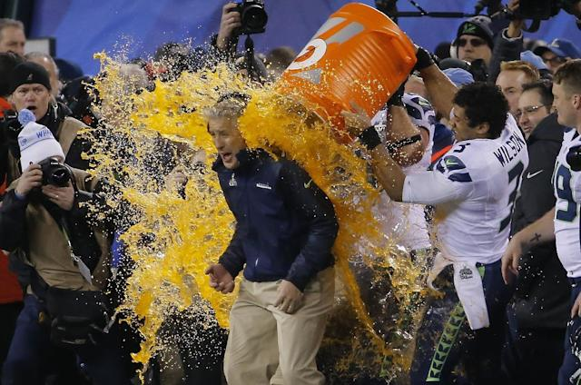 Seattle Seahawks quarterback Russell Wilson (3) dumps Gatorade on head coach Pete Carroll late in the game against the Denver Broncos during the second half of the NFL Super Bowl XLVIII football game Sunday, Feb. 2, 2014, in East Rutherford, N.J. Seattle won 43-8. (AP Photo/Matt York)