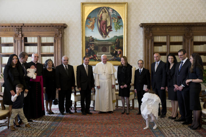 Pope Francis poses for photographers with Malta's President George Abela, at this left, and members of his family and delegates during a private audience in the Pontiff's studio, at the Vatican, Friday, March 21, 2014. (AP Photo/Andrew Medichini, Pool)