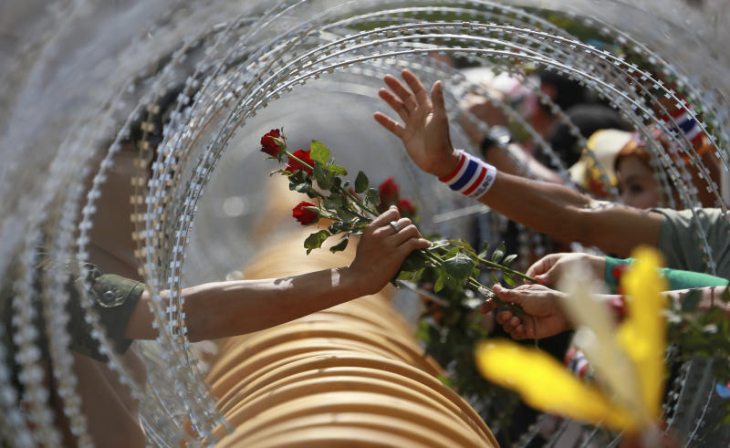 An anti-government protester gives a rose to a Thai soldier at the Defense Ministry during a rally in Bangkok Thursday, Nov. 28, 2013. Thailand's embattled prime minister begged protesters who have staged the most sustained street rallies in Bangkok in years to call off their demonstrations Thursday and negotiate an end to the nation's latest crisis. (AP Photo/Wason Wanichakorn)