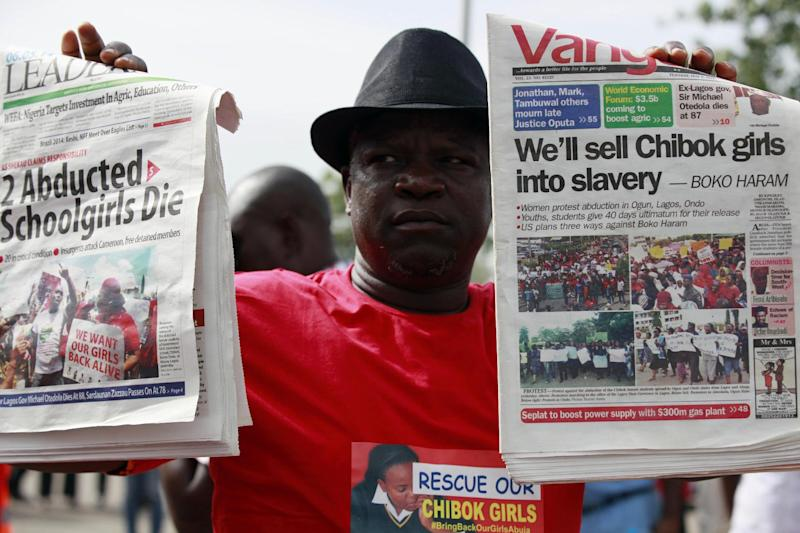 "A man display copies of local newspapers during a demonstration calling on the government to rescue kidnapped school girls from Chibok government secondary school, outside the defense headquarters, in Abuja, Nigeria, Tuesday, May 6, 2014. The plight — and the failure of the Nigerian military to find them — has drawn international attention to an escalating Islamic extremist insurrection that has killed more than 1,500 so far this year. Boko Haram, the name means ""Western education is sinful,"" has claimed responsibility for the mass kidnapping and threatened to sell the girls. The claim was made in a video seen Monday. The British and U.S. governments have expressed concern over the fate of the missing students, and protests have erupted in major Nigerian cities and in New York. (AP Photo/ Sunday Alamba)"