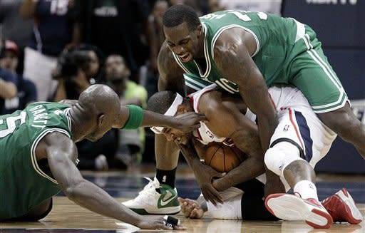 Atlanta Hawks' Josh Smith, center, is fouled by Boston Celtics' Brandon Bass while chasing down a loose ball next to Celtics' Kevin Garnett, left, during the fourth quarter of Game 1 of an opening-round NBA basketball playoff series Sunday, April 29, 2012, in Atlanta. Atlanta won 83-74. (AP Photo/David Goldman)