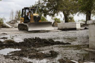 A clean worker bulldozes gravel in a heavily damaged cemetery in Ironton, La., Monday, Sept. 27, 2021. A month after Hurricane Ida, small communities along Louisiana's southeastern coast are still without power or running water. Some residents have lost most of their possessions to the storm's floodwaters. (AP Photo/Gerald Herbert)