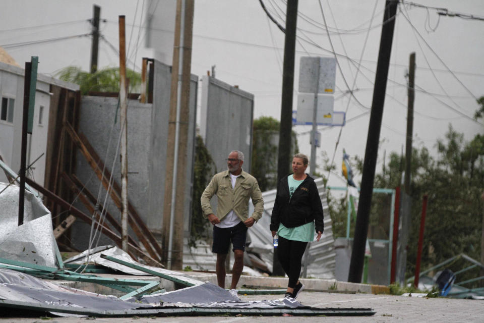 Tourists walk past debris littering the street after Hurricane Zeta's landfall in Playa del Carmen, Mexico, early Tuesday, Oct. 27, 2020. Zeta is leaving Mexico's Yucatan Peninsula on a path that could hit New Orleans Wednesday night. (AP Photo/Tomas Stargardter)