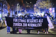 "Participants in a demonstration against curfew restrictions walk through Nordstadt with a banner reading ""For something better than back to normal"" during the nightly curfew, in Hanover, Germany, Saturday, April 24, 2021. Federal coronavirus emergency curfew regulations have been in effect as of Saturday. This includes, among other things, curfew restrictions between 10 p.m. and 5 a.m. (Ole Spata/dpa via AP)"