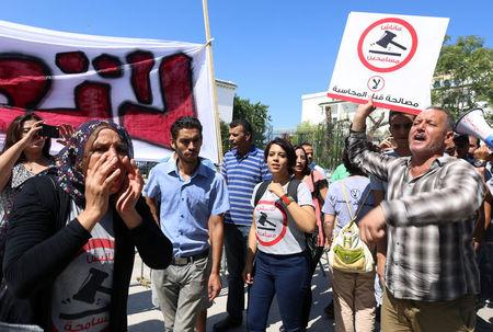 People demonstrate against a bill that would protect from prosecution those accused of corruption in Tunis