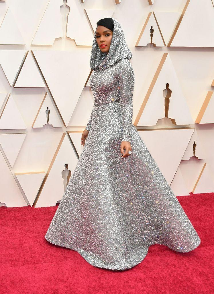 <p>Never one to shy from a dramatic look, Janelle Monáe brought it in a custom crystal-laquered silk lamé tulle mesh evening dress. The real pièce de résistance? A draped hood. The gown is fully hand-embroidered with over 168,000 Swarovski crystals.</p>