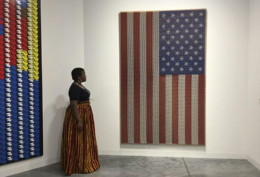 "An exhibitor stands next to a piece by Rob Pruitt titled ""Pledge Allegiance (Flammable),"" which is made of sticks hand-painted to look like matches"