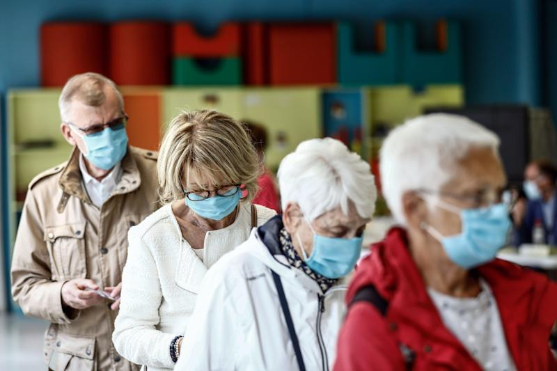 Voters wearing face masks wait to cast their ballot for the the second round of the mayoral elections on June 28, 2020 at a polling station in Le Havre, western France, amid the crisis linked with the Covid-19 pandemic caused by the novel coronavirus. (Photo by Sameer Al-DOUMY / AFP) (Photo by SAMEER AL-DOUMY/AFP via Getty Images)