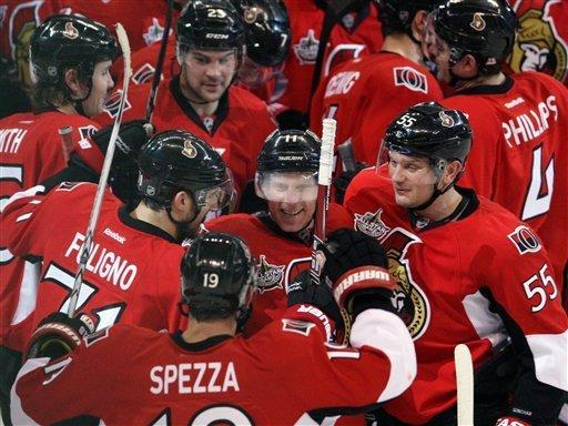 Ottawa Senators' Daniel Alfredsson (11), of Sweden, is congratulated by teammates as he celebrates his 400th career goal to win in overtime against the Calgary Flames during NHL hockey game action in Ottawa, Ontario, Friday, Dec. 30, 2011. (AP Photo/The Canadian Press, Fred Chartrand)