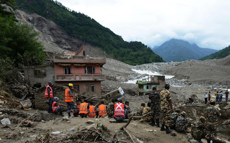 Nepalese rescue personnel gather during a recovery operation following a landslide on the Sukoshi river on August 6, 2014 (AFP Photo/Prakash Mathema)
