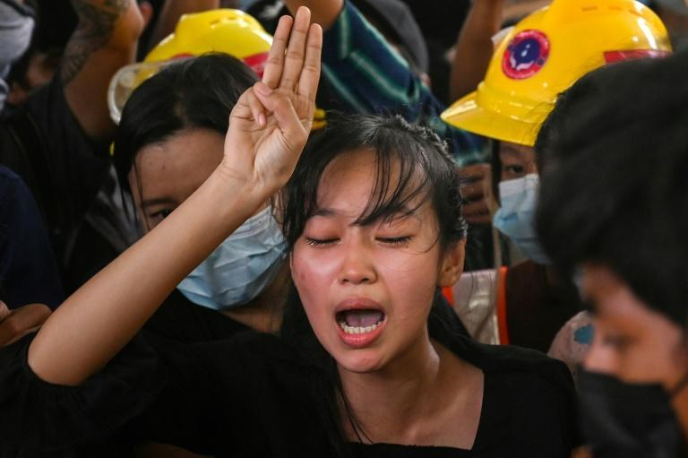 The sister of Chit Min Thu, who died during an anti-coup demonstration on March 11, cries as she makes the three-finger salute during her brother's funeral in Yangon