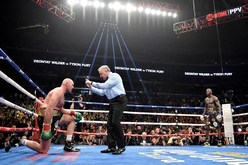 Tyson Fury receives a count from the referee in his first fight with Deontay Wilder.