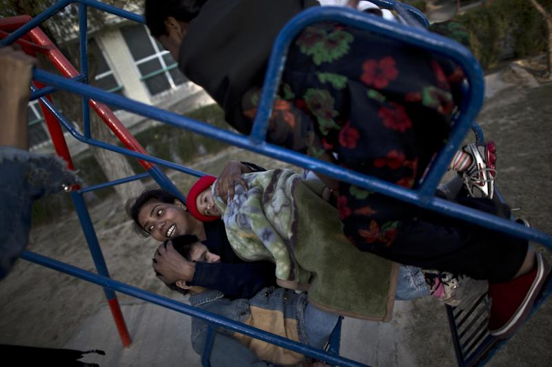In this Sunday, Feb. 16, 2014, photo, Pakistani nurse Farzana Yassmine, 31, enjoys a swing ride holding Caleb, 1, and Mariam 11, and other patients who live at St. Joseph's Hospice, at the garden of the hospice, in Rawalpindi, Pakistan. Mohammed Aqeel spent weeks at home in Pakistan waiting for death after suffering a debilitating spinal cord injury in a car crash before friends suggested he come to St. Joseph's Hospice on the outskirts of the capital, Islamabad. Now 13 years later, his life and those of some 40 others who live on its grounds might be changed forever as this hospital of last resort faces closure over its rising debts. (AP Photo/Muhammed Muheisen)