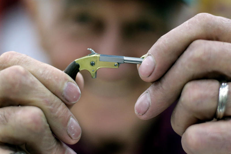 FILE - In this, May 21, 2016, file photo, Bob McGinnis, of Cross Plains, Wis., holds a miniature gun he has made at a display of the Miniature Arms Society at the National Rifle Association convention in Louisville, Ky. The convention, that started in 1871 as a group devoted to hunting, shooting sports and gun safety, has evolved into one of the most powerful forces in American politics. (AP Photo/Mark Humphrey, File)