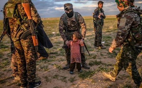 A member of the SDF holds a toddler during a security check of her and her mother (unseen) after they left Isil's last holdout of Baghuz - Credit: AFP