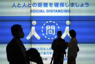 People wearing protective masks to help curb the spread of the coronavirus stand near a public awareness notice for social distancing Thursday, May 13, 2021, in Tokyo. The Japanese capital confirmed more than 1,000 new coronavirus cases on Thursday. (AP Photo/Eugene Hoshiko)