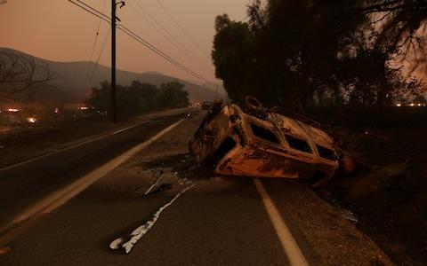 The burned remains of crashed cars are seen at night on a country road as strong winds push the Thomas Fire across thousands of acres near Santa Paula - Credit: Reuters