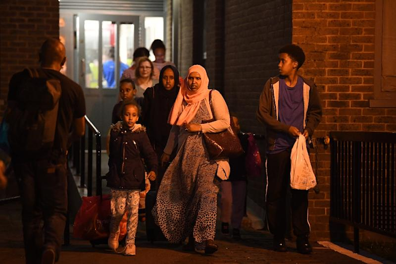 A family leave the Taplow Tower residential block on the Chalcots Estate in north London on June 23, 2017 as residents are evacuated because of fire safety concerns (AFP Photo/Justin TALLIS)