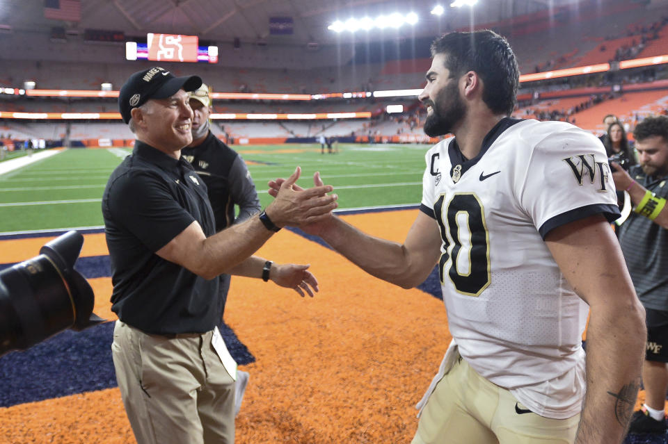 Wake Forest head coach Dave Clawson, left, celebrates with quarterback Sam Hartman after a 40-37 overtime win against Syracuse in an NCAA college football game in Syracuse, N.Y., Saturday, Oct. 9, 2021. (AP Photo/Adrian Kraus)
