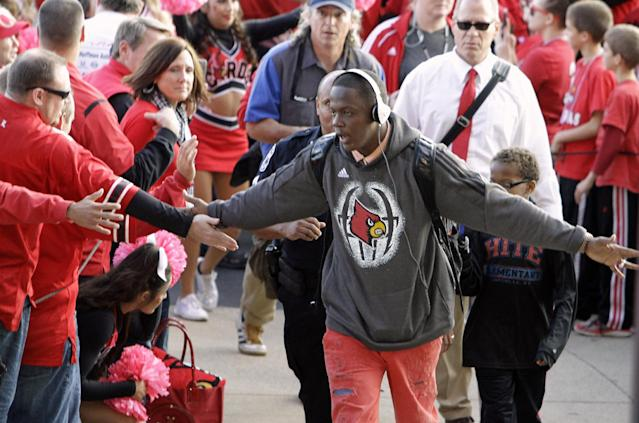 Louisville quarterback Teddy Bridgewater greets fans as the team arrives at Cardinal Stadium for an NCAA college football game against Central Florida in Louisville, Ky., Friday, Oct. 18, 2013. (AP Photo/Garry Jones)