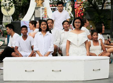 Filipino theatre artists perform, in front of a mock coffin, a short musical about the killings under the Philippine government's anti-drug campaign, in Pandacan city, metro Manila, Philippines April 2, 2017. REUTERS/Romeo Ranoco