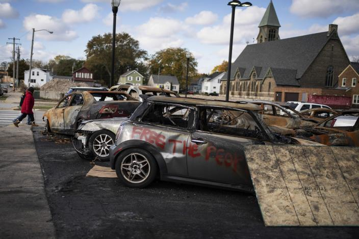 People walk past burnt vehicles in Kenosha, Wis., Friday, Oct. 30, 2020. The trouble in Kenosha began on Aug. 23 when a Kenosha police officer, responding to a call about a domestic dispute, was caught on video shooting Jacob Blake repeatedly in the back at close range. Blake, a Black man, survived but is partially paralyzed. The August shootings have spurred a spike in political involvement in Kenosha, with the formation of activism and waves of new voters signing up. (AP Photo/Wong Maye-E)