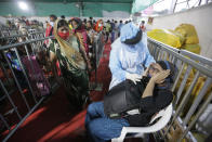 An Indian woman reacts as a health worker takes a nasal swab sample to test for COVID-19 at a facility erected at a railway station to screen people coming from outside the city, in Ahmedabad, India, Friday, Sept. 18, 2020. India's coronavirus cases jumped by another 96,424 in the past 24 hours, showing little sign of leveling. India is expected to have the highest number of confirmed cases within weeks, surpassing the United States, where more than 6.67 million people have been infected. (AP Photo/Ajit Solanki)