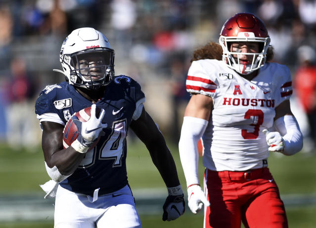 Connecticut running back Kevin Mensah (34) gains yardage against Houston linebacker Jordan Carmouche (8) during the second half of an NCAA college football game, Saturday, Oct. 19, 2019, in East Hartford, Conn. (AP Photo/Stephen Dunn)