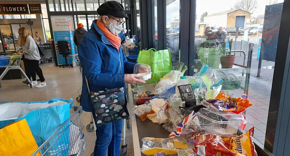 A woman unwrapping groceries in ALDI to show the amount of plastic used.