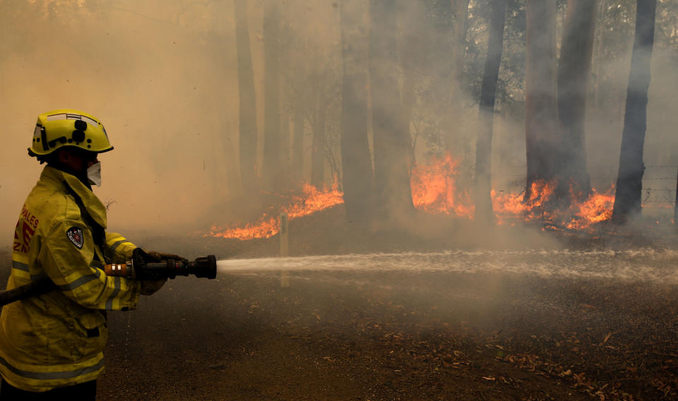 A firefighter is seen trying to extinguish a blaze. Source: AAP