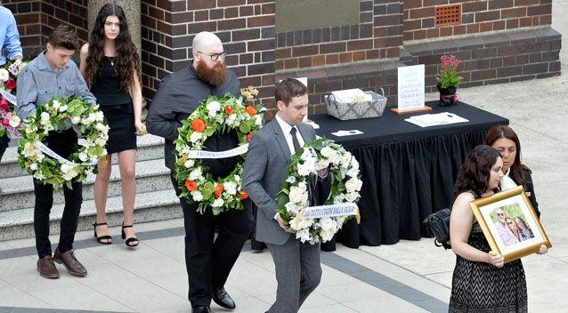 The mourners carried the wreaths in a procession after the funeral service on Wednesday. Photo: AAP