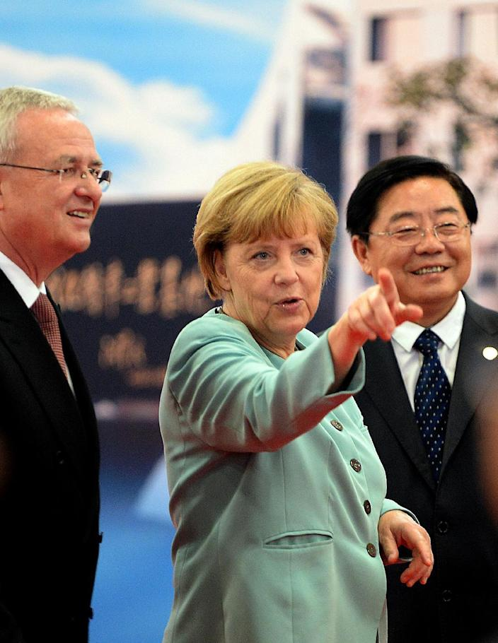 Angela Merkel with Volkswagen CEO Martin Winterkorn (left) and FAW Group CEO Xu Jianyi (right) during her visit to the FAW-Volkswagen plant in Chengdu, southwest China's Sichuan province on July 6, 2014 (AFP Photo/Goh Chai Hin)