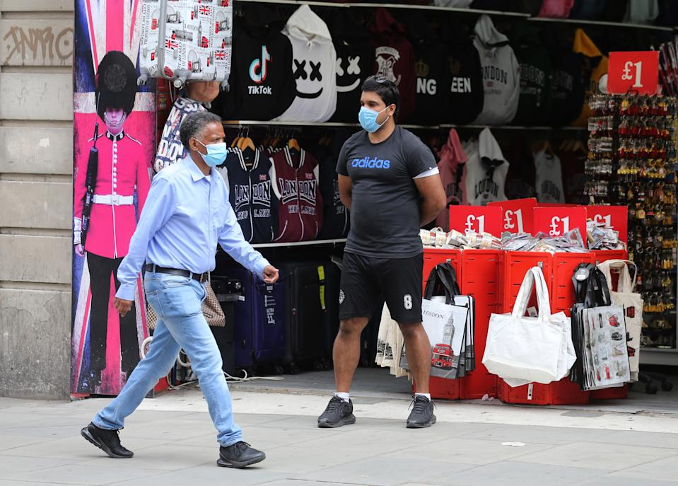 Shoppers wearing face masks walk past a souvenir store on Oxford Street, London