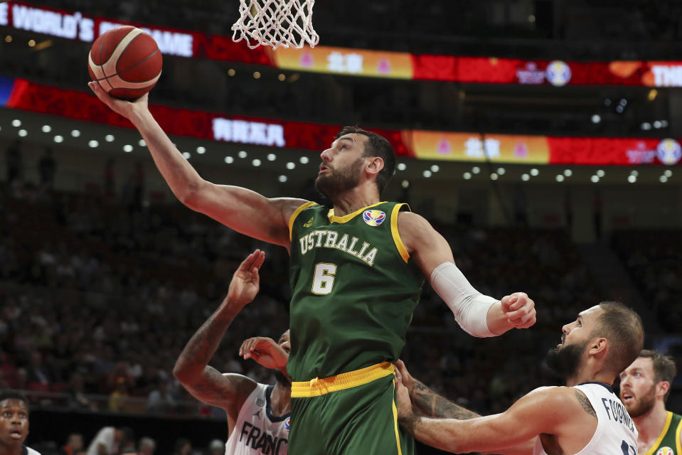 FILE - In this Sept. 15, 2019, file photo, Andrew Bogut of Australia puts up a shot over Amath M'Baye, left, and Evan Fournier of France during their third placing match for the FIBA Basketball World Cup at the Cadillac Arena in Beijing. Bogut announced Tuesday, Dec. 1, 2020 that he is calling quits on his bid for an Olympic medal and has decided to retire after 15 years in professional basketball. (AP Photo/Ng Han Guan, File)