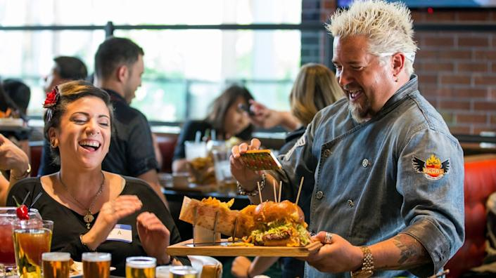 """Celebrity chef Guy Fieri serves a sandwich with a smile at his restaurant at the Linq resort, before the pandemic. <span class=""""copyright"""">(Erik Kabik)</span>"""