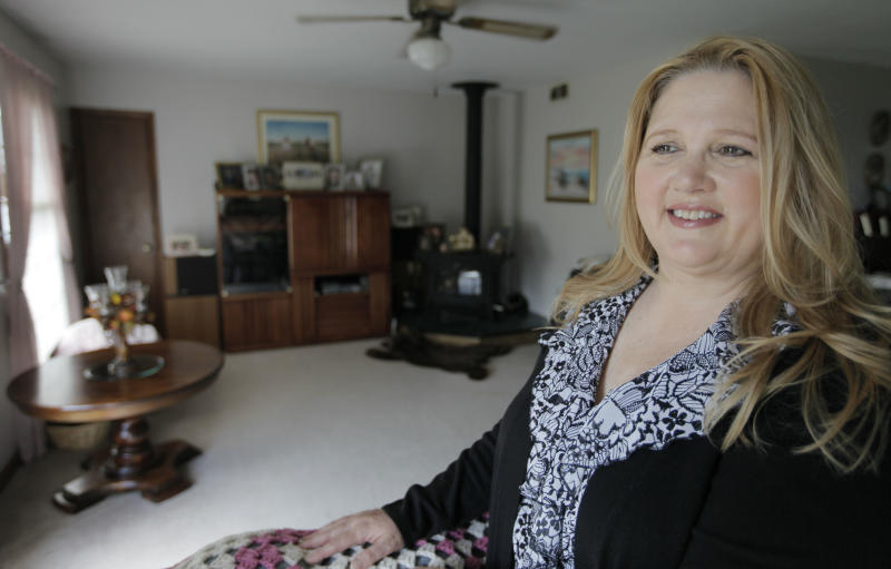 Michelle Chesney-Offutt, poses in her home before leaving for work as an insurance customer service representative, Thursday, March 22, 2012, in Sandwich, Ill. Chesney-Offutt, who was unemployed for nearly three years before landing a job, said a recruiter who responded to her online resume two years ago liked her qualifications and was set to schedule an interview. But he backed away, she said, when he learned she had been out of work for 13 months. The employer he represented would not consider applicants who were unemployed for more than six months, she said. More than a dozen states are considering legislation that would forbid employers from refusing to hire workers just because they've been unemployed for months or years. (AP Photo/M. Spencer Green)