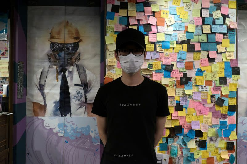 """KC, owner of Mainichi restaurant, poses for a photo in front of a """"Lennon Wall"""" in Hong Kong"""