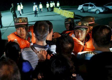 Family members of passengers of a sunken cruise ship push a cordon of paramilitary police as they march toward the site of the sunken ship in the Jianli section of Yangtze River, Hubei province, China, June 3, 2015. REUTERS/Kim Kyung-Hoon