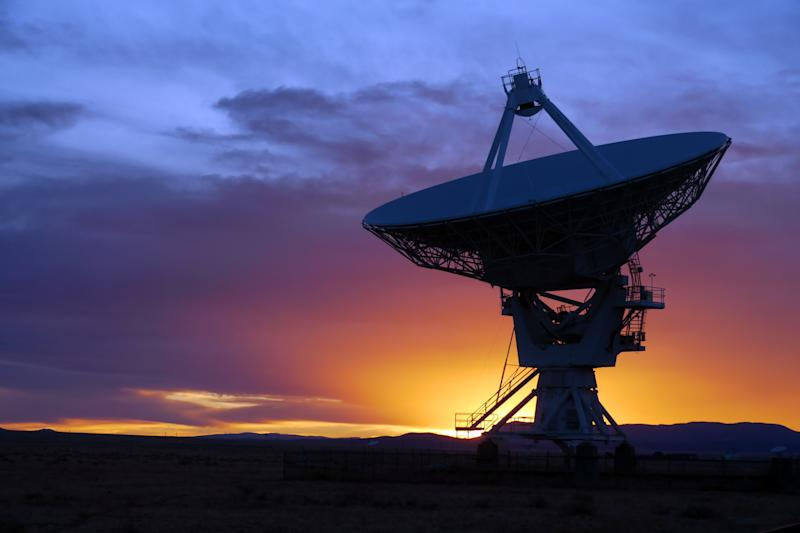 A satellite dish pointed up to space in front of a sunset.