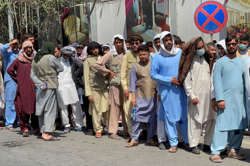 FILE PHOTO: Afghans line up outside a bank to take out their money after Taliban takeover in Kabul
