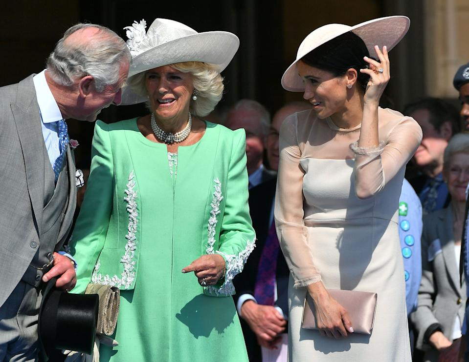 TOPSHOT - Britain's Prince Charles, Prince of Wales (L) and his wife Britain's Camilla, Duchess of Cornwall (C), talk with Britain's Meghan, Duchess of Sussex, as her husband Britain's Prince Harry, Duke of Sussex (unseen), speaks during the Prince of Wales's 70th Birthday Garden Party at Buckingham Palace in London on May 22, 2018. - The Prince of Wales and The Duchess of Cornwall hosted a Garden Party to celebrate the work of The Prince's Charities in the year of Prince Charles's 70th Birthday. (Photo by Dominic Lipinski / POOL / AFP)        (Photo credit should read DOMINIC LIPINSKI/AFP via Getty Images)