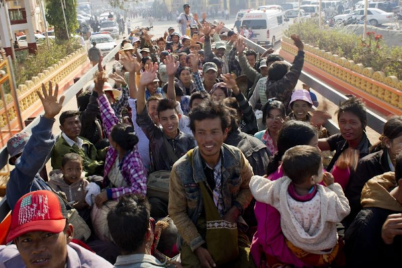 Residents who fled from conflict areas near the Myanmar and Chinese border wave onboard a truck transporting them to a refugee camp in Mandalay, Myanmar on February 21, 2015 (AFP Photo/Ye Aung Thu)