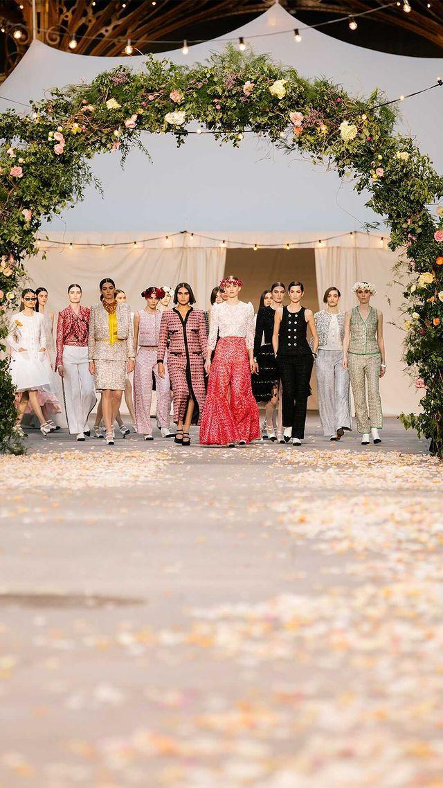 """<p>Creative Director Virginie Viard recreated a summer village wedding in the Grand Palais for the SS21 Couture show. With Penélope Cruz, Marion Cotillard and Lily-Rose Depp as esteemed guests.</p><p>'I knew we couldn't organise a big show, that we would have to invent something else, so I came up with the idea of a small cortege that would come down the stairs of the Grand Palais and pass beneath arches of flowers. Like a family celebration, a wedding.' Viard said.</p><p>The simple, but no less moving set, feels somewhat fantastical in a year where <a href=""""https://www.elle.com/uk/fashion/celebrity-style/g30864/wedding-dress-inspiration-haute-couture-fashion-week/"""" rel=""""nofollow noopener"""" target=""""_blank"""" data-ylk=""""slk:weddings are limited"""" class=""""link rapid-noclick-resp"""">weddings are limited</a>, bringing hope to <a href=""""https://www.elle.com/uk/haute-couture-fashion-week/"""" rel=""""nofollow noopener"""" target=""""_blank"""" data-ylk=""""slk:Haute Couture fashion week"""" class=""""link rapid-noclick-resp"""">Haute Couture fashion week</a>. </p><p><a href=""""https://www.instagram.com/p/CKgjlq0ovZK/"""" rel=""""nofollow noopener"""" target=""""_blank"""" data-ylk=""""slk:See the original post on Instagram"""" class=""""link rapid-noclick-resp"""">See the original post on Instagram</a></p>"""