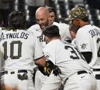 Pittsburgh Pirates catcher Jacob Stallings is mobbed by teammates after hitting a two-run home run against the San Francisco Giants in a baseball game Saturday May 15, 2021, in Pittsburgh. (Peter Diana/Pittsburgh Post-Gazette via AP)