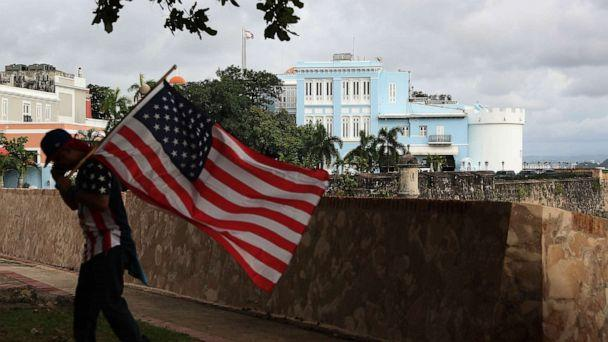 PHOTO: A man carrying a U.S. flag walks past the governor's mansion where Ricardo Rossello, the Governor of Puerto Rico lives in Old San Juan, Puerto Rico, Aug. 1, 2019. (Joe Raedle/Getty Images)