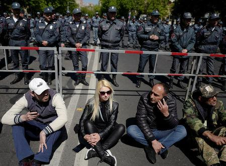 Demonstrators sit in front of riot police during a protest against Armenia's ruling Republican party's nomination of former President Serzh Sarksyan as its candidate for prime minister, in Yerevan, Armenia April 16, 2018. PAN Photo/Vahan Stepanyan/Handout via REUTERS