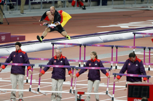 Germany's Robert Harting jumps over a hurdle as he celebrates winning the men's discus throw final during the London 2012 Olympic Games at the Olympic Stadium August 7, 2012. Harting won gold ahead of Iran's Ehsan Hadadi who took silver and Estonia's Gerd Kanter who won bronze. REUTERS/Stefan Wermuth (BRITAIN - Tags: SPORT ATHLETICS OLYMPICS)